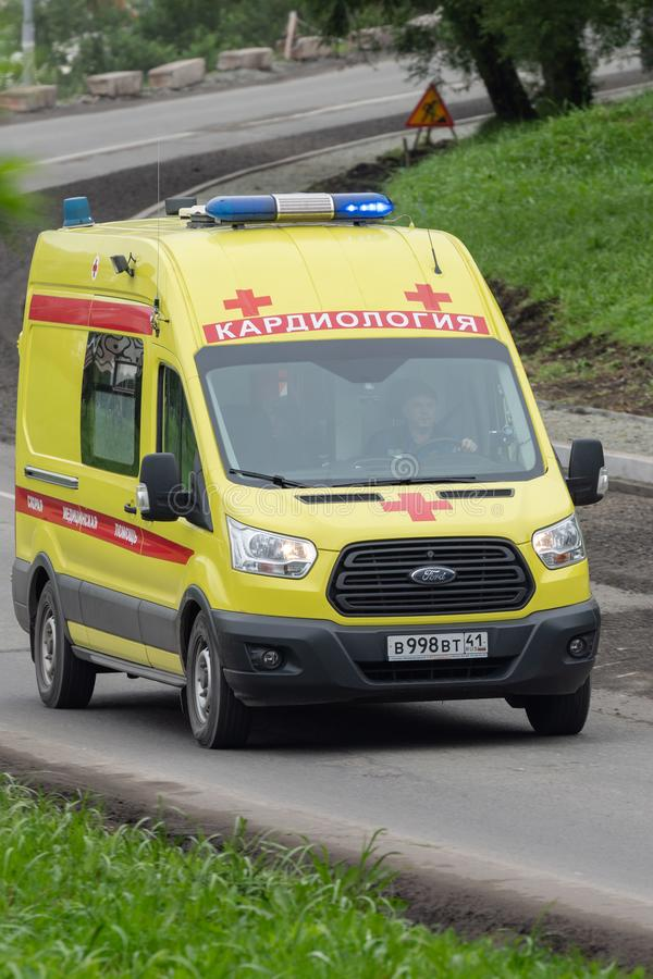 Yellow State Cardiology Ambulance van with siren, blue flashing lights speed driving on city street road to help patient. Petropavlovsk City, Kamchatka royalty free stock image