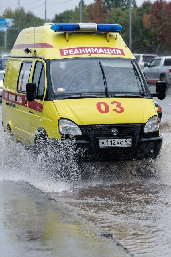 Emergency Ambulance Reanimation Medical vehicle driving on road over muddy puddle, splashing wat. Yellow State Emergency Ambulance Reanimation Medical van royalty free stock photo