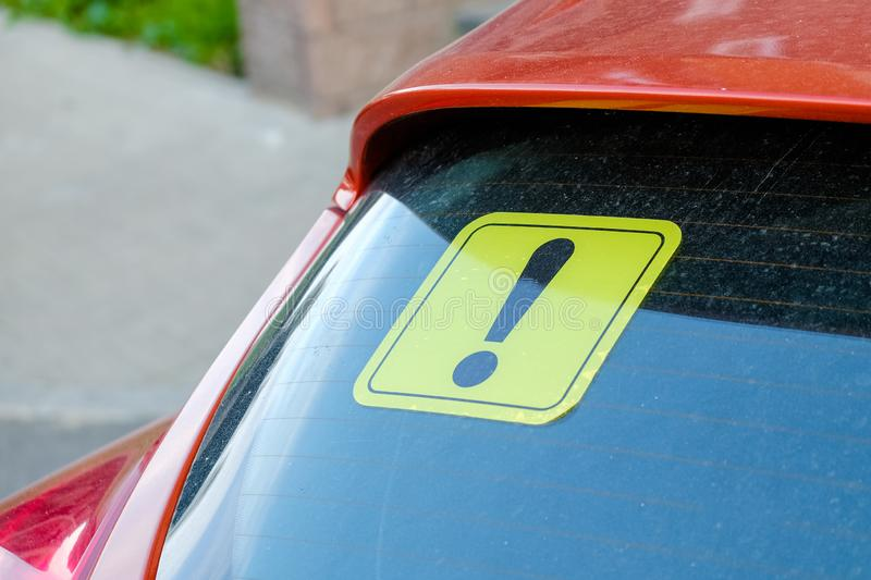 Yellow sticker with an exclamation point on the car`s glass. A newbie driver`s sign. Close up stock photo