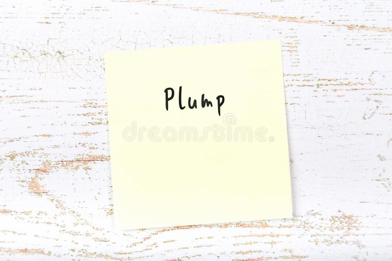 Yellow sticky note with handwritten word plump.  stock photo