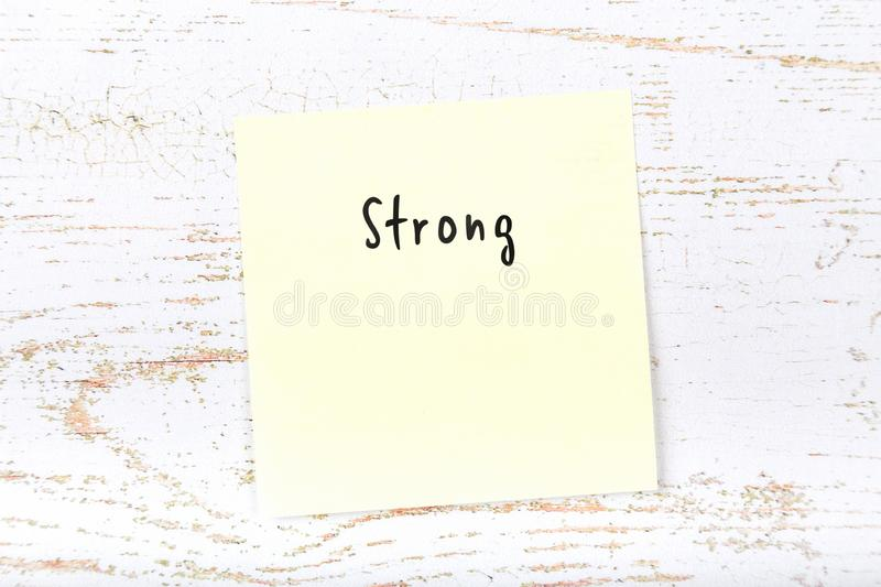 Yellow sticky note with handwritten word strong.  royalty free stock photos