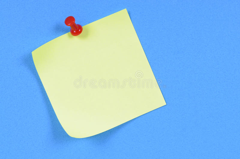 Blank yellow post-it style office sticky note pinned to blue background, copy space royalty free stock images