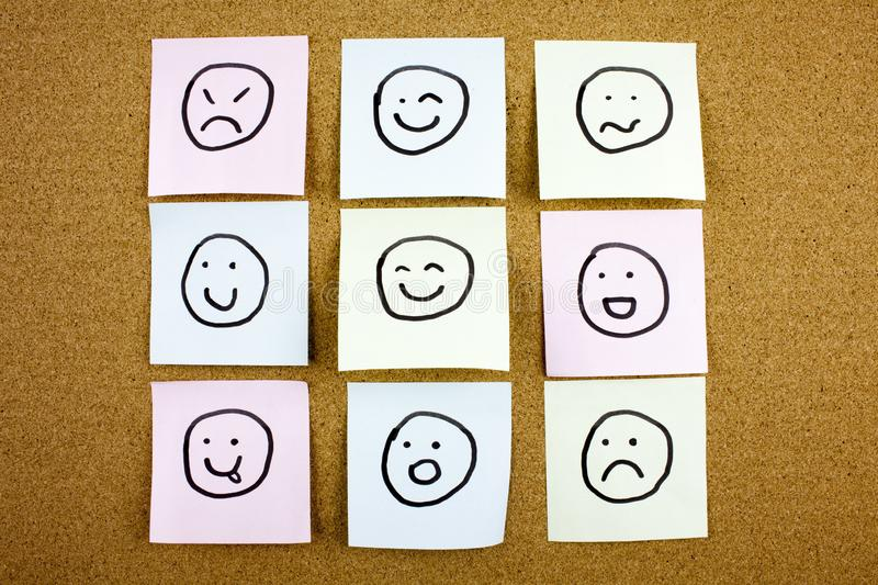 A yellow sticky note post it writing, caption, inscription Crumpled sticky note emoticons smileys in black ext on a. Sticky note pinned to a cork board royalty free stock photo