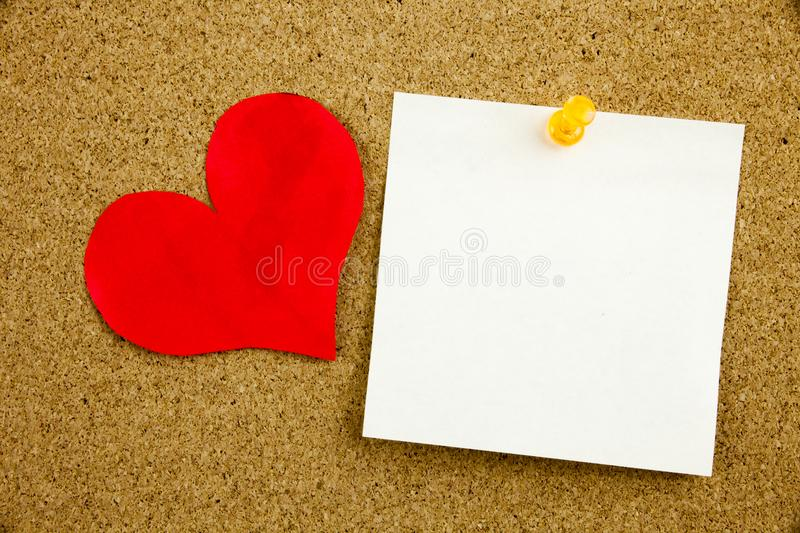 A yellow sticky note post it writing, caption, inscription empty in black ext on a sticky note pinned to a cork notice board stock image
