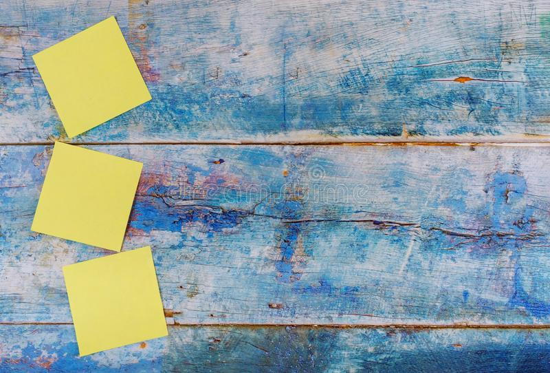 Yellow sticky notes empty square reminder in the blue old wooden background. Yellow sticky empty square notes reminder in the blue old wooden background, paper royalty free stock photo