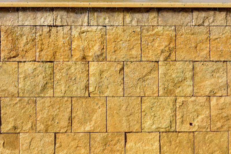 Yellow stone blocks with water flowing background. Yellow stone blocks texure. royalty free stock photo