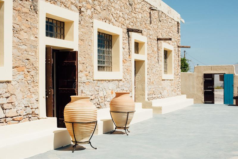 Yellow stone building with square windows and with wine jugs. On Santorini stock photos