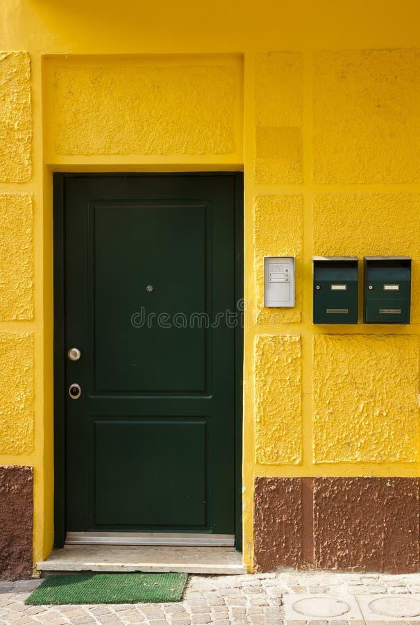 Yellow stone house green door, Bardolino, Italy royalty free stock photos