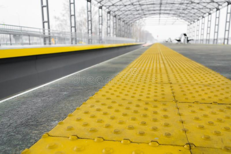Yellow stop line for blind  people at railroad station in perspective royalty free stock photos