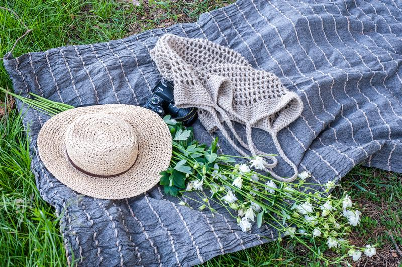 Yellow straw hat, flowers bouquet, a camera and knitted bag lays on grey beach mat on the grass outdoor, isometric view royalty free stock photography
