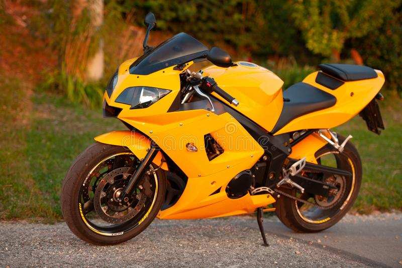 Yellow street motor bike parked on edge of a road.  royalty free stock photos