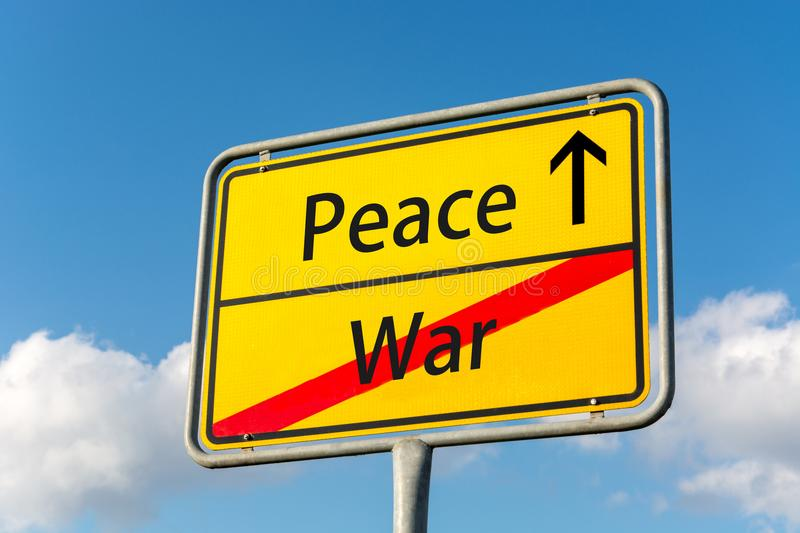 Yellow street sign with peace ahead leaving war behind royalty free stock photo
