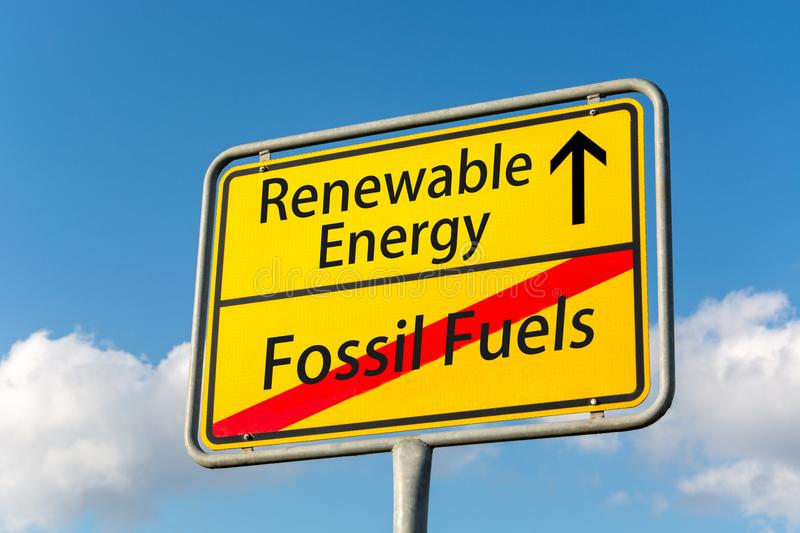 Yellow street sign with renewable energy ahead leaving fossil fuels behind. Close up royalty free stock photo