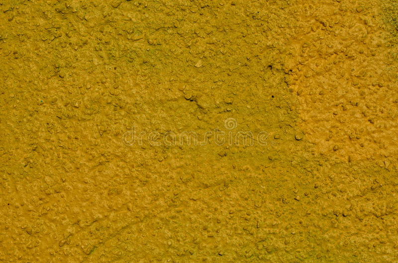 Yellow stucco. Wall with stucco coating airbrushed with yellow graffiti paint stock images