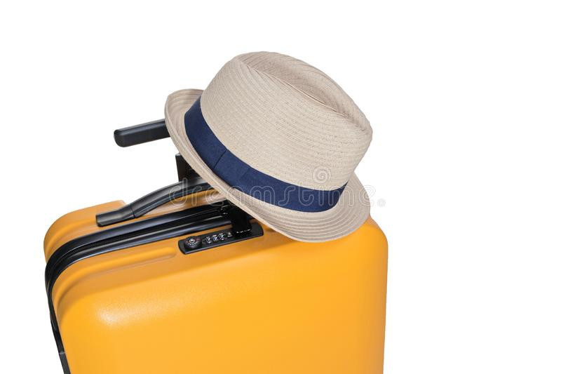yellow suitcase with a combination lock with numbers 777 on it..Summer time -Travel bag and straw hat on top royalty free stock photos