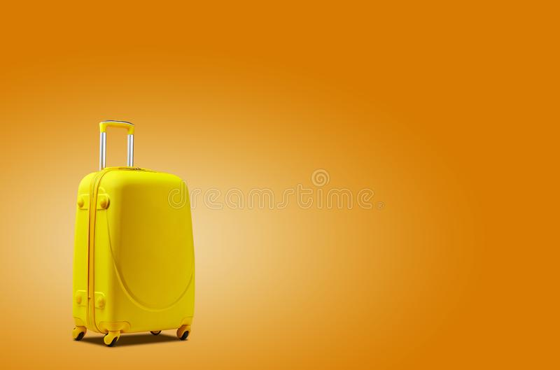 Yellow suitcase is standing against an orange background. A realistic shadow is drawn in under it. Collage. Copy space. For your text or images, close-up stock image