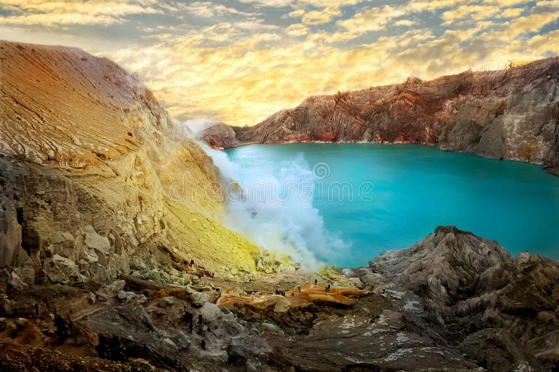 Yellow sulfur rocks and the blue sulfur lake of the crater of the Ijen volcano at dawn. Poisonous sulfur smoke. Mountain volcanic landscape stock photography