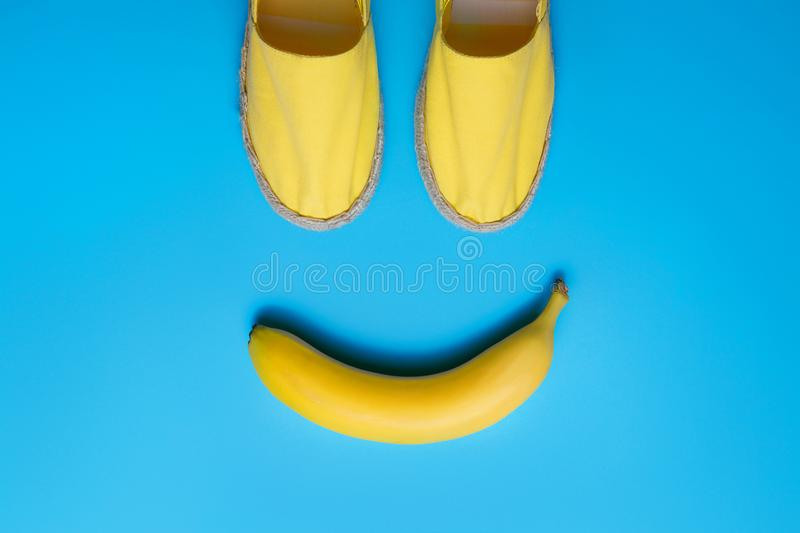Yellow summer shoes and banana on the blue background. Smile emoji concept. stock photos