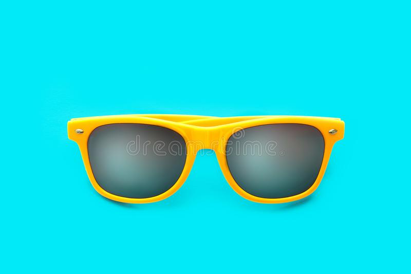 Yellow sunglasses in intense cyan blue background. Minimal image concept for ready for summer, sun protection, hot days tropical. Yellow sunglasses in intense royalty free stock image