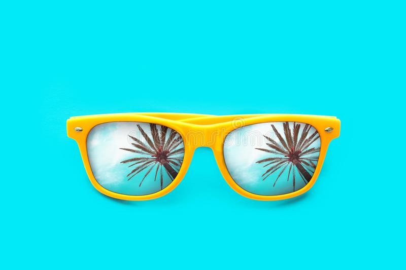 Yellow sunglasses with palm tree reflections in intense cyan blue background. Minimal image concept for ready for summer. Sun protection, hot days and tropical stock photos