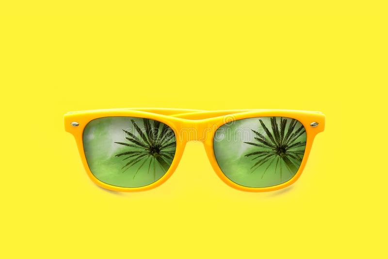 Yellow sunglasses summer concept with palm tree reflections isolated in yellow background. stock image