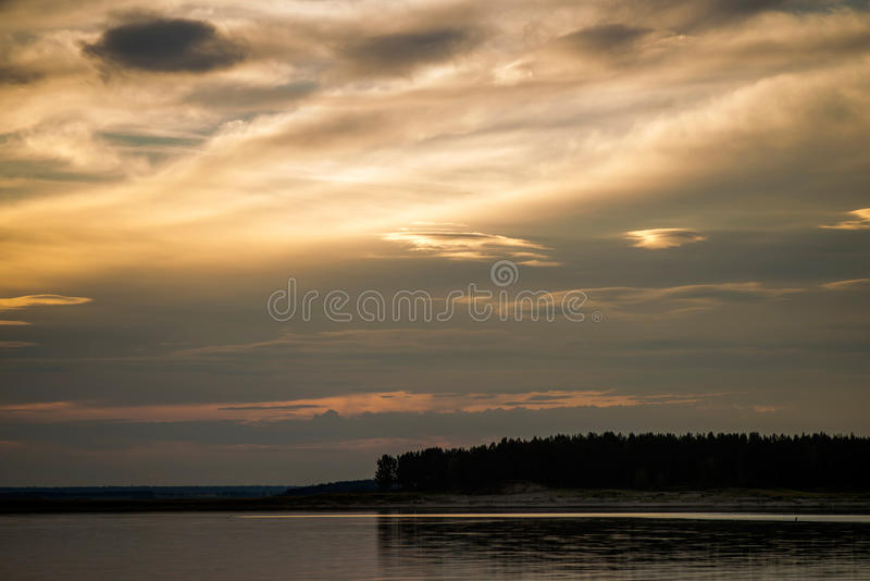 Yellow sunset over forest lake. Orange Sunset on the forest lake stock photo