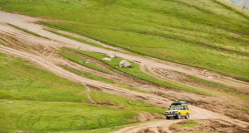 Yellow SUV Car On Off Road In Spring Hilly Landscape. Drive And Travel Concept.  royalty free stock photo