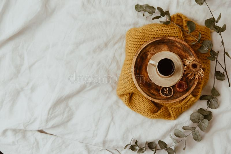 Yellow sweater, wooden tray and coffee cup on bed. Instagram still life trendy photo. stock photo