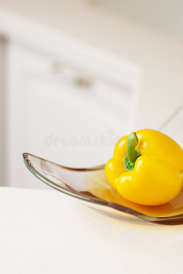 Yellow sweet pepper on kitchen's table royalty free stock photography