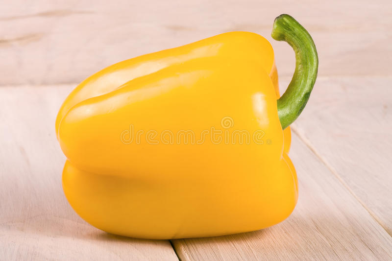 Yellow sweet pepper on white wooden background.  royalty free stock images