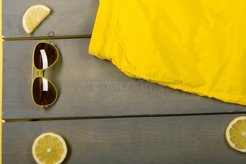 Yellow Swim Trunks,. Man beach accessories on wooden background. Yellow Swim Trunks, aviator sunglasses between parts of lemons on grey wooden board stock photo