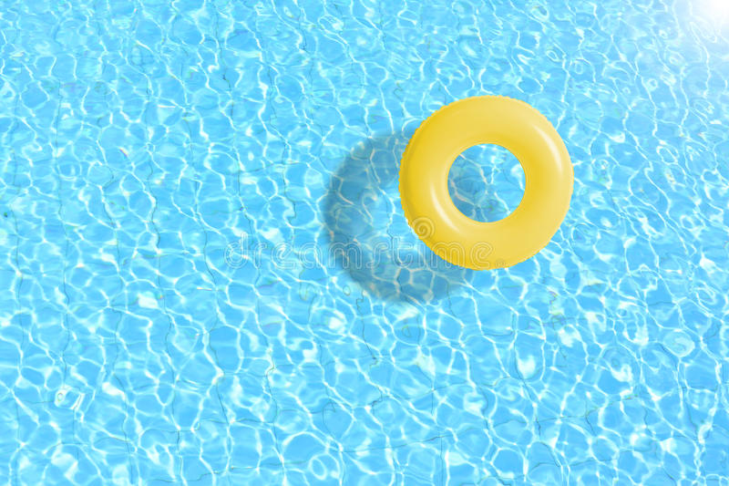 Yellow swimming pool ring float in blue water. stock photo
