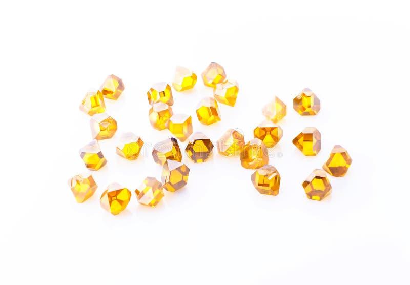 Yellow synthetic diamonds in macro. The scattered yellow synthetic diamonds in macro on a white background royalty free stock image