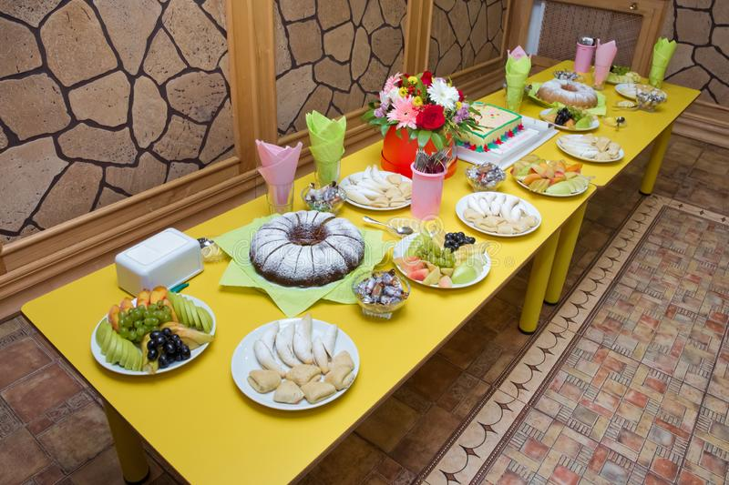 Yellow table . Holiday table for kids in the kindergarden . homemade bundt cake with icing sugar. Pickled apple and pear. Black stock photos