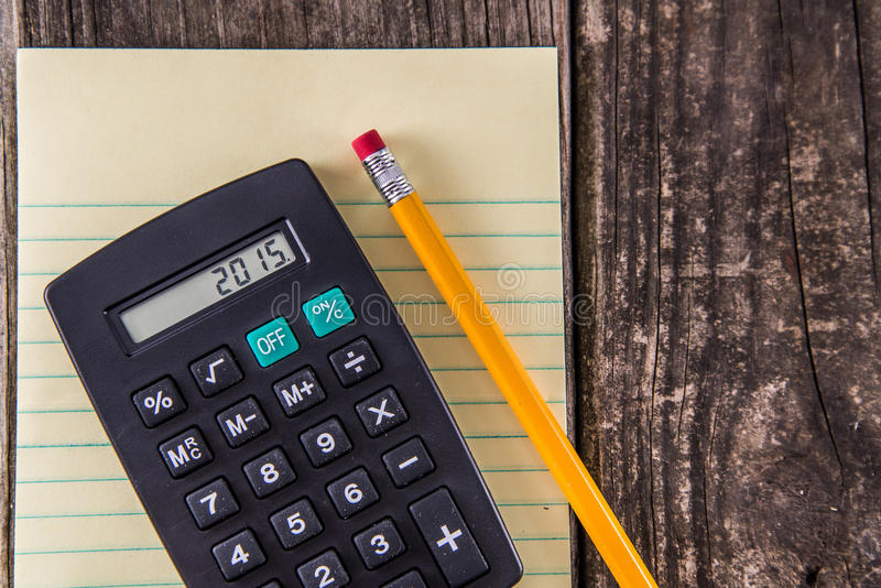 Yellow Tablet Pencil & Calculator on Vintage Desk royalty free stock image