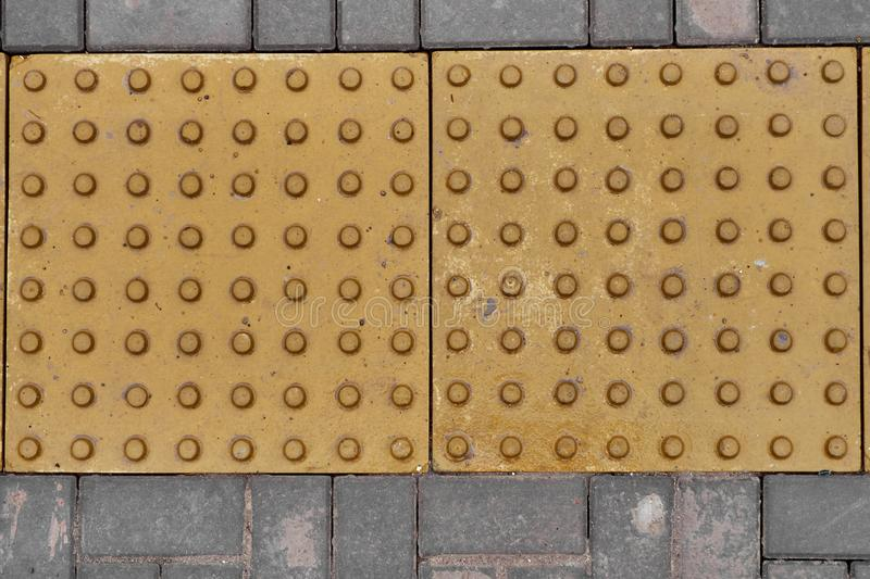 Yellow tactile tile for people with poor eyesight royalty free stock photos