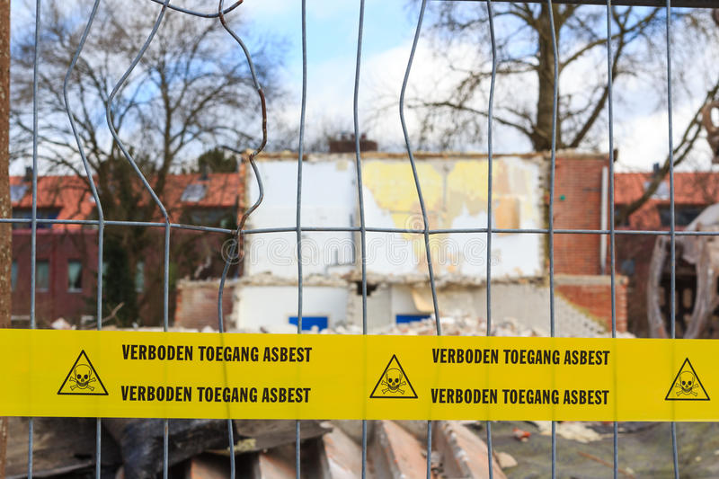 Yellow tape with Dutch text no trespassing asbesto stock image
