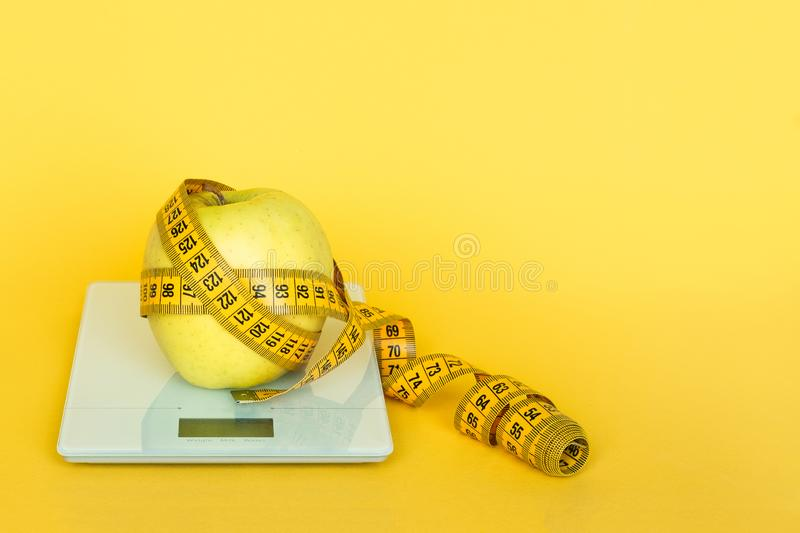 Yellow tape-line and apple on the digital kitchen scale on a yellow background. Concept of overeating, excess weight and obesity. stock photo