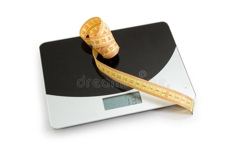 Tape-line on kitchen scales, concept of excess weight royalty free stock images