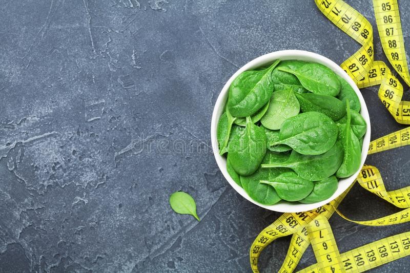 Yellow tape measure and green spinach leaves from above. Diet food concept. stock photo
