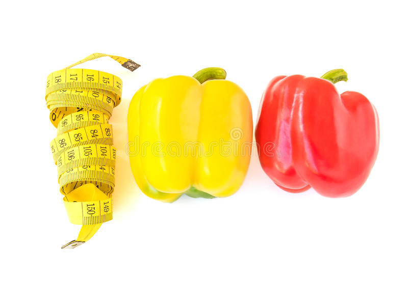 Yellow tape measure and sweet pepper on white background. Healthy lifestyle concept stock photos