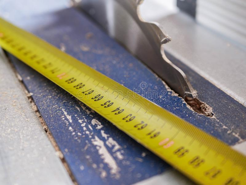 Yellow tape measurer on dusty circular saw, royalty free stock photo