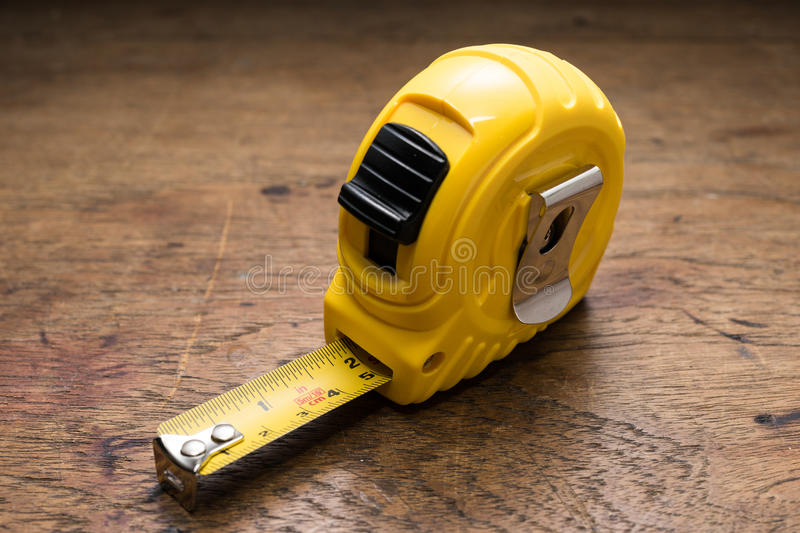 Yellow Tape Ruler. On Wooden table royalty free stock images