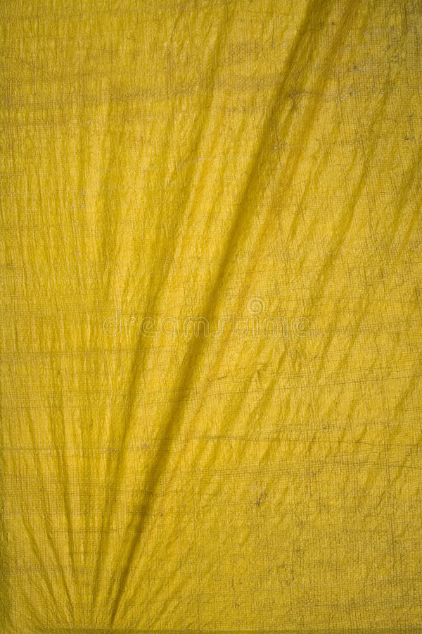 Yellow tarpaulin with folds. Background with text space royalty free stock photo