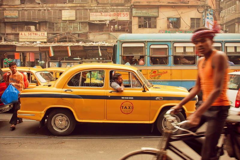 Yellow taxi car, buses and cyclists driving on the busy street of indian city. KOLKATA, INDIA - JAN 13: Yellow taxi car, buses and cyclists driving on the busy royalty free stock photo