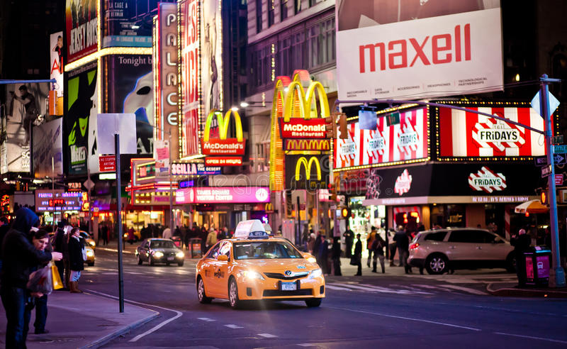 Yellow taxi car riding through Times Square royalty free stock image