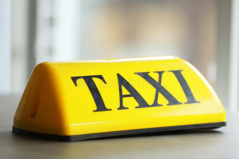 Yellow taxi roof sign on gray table royalty free stock photo