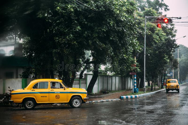 Yellow taxi with traffic jam on the road and waiting for green traffic light in the morning with rain at Kolkata, India royalty free stock photo