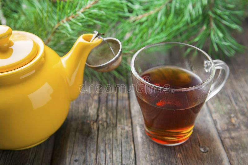 Yellow teapot with glass cup of tea royalty free stock photo