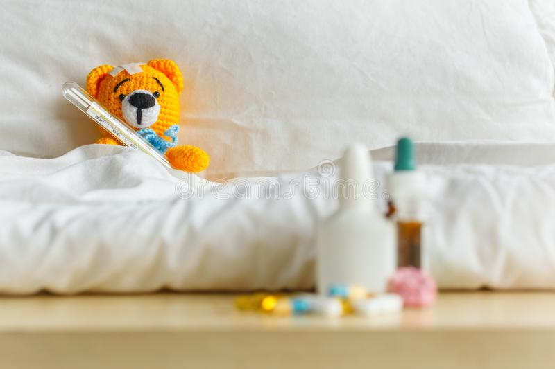 Yellow teddy bear with thermometer and plaster on head in white bedroom and medicament on a table.  stock photography